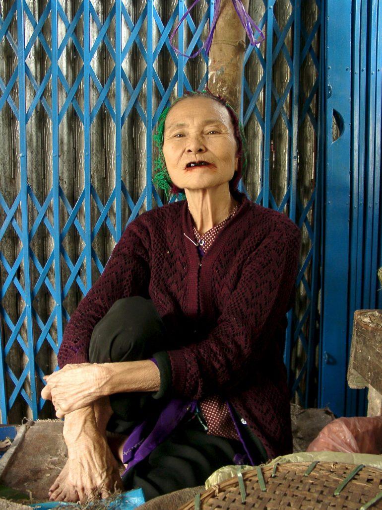 Alte Frau vor einer blauen Tür beim joggen in Saigon