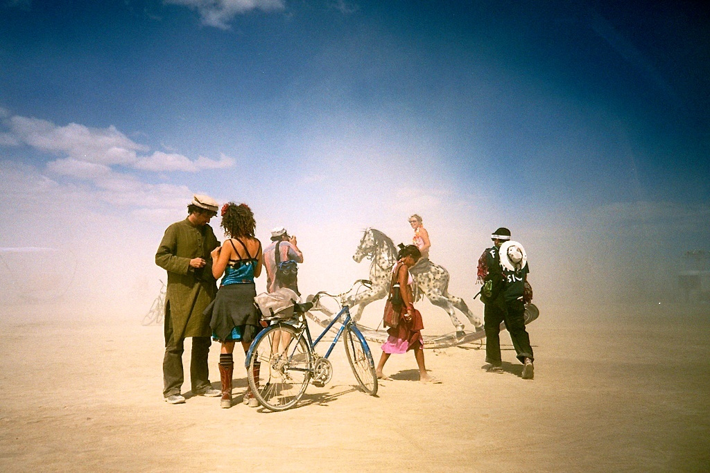 Festivals around the world: People and a toy horse in the desert