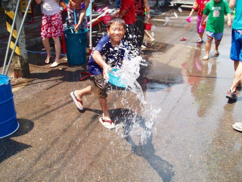 Beste Festivals: Kind mit Wassereimer während Songkran in Chiangm, Thailand