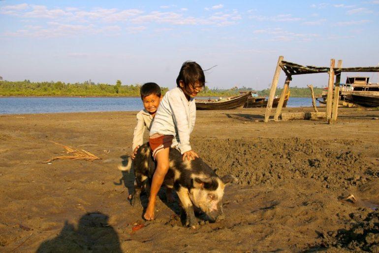 Jahrmarkt in Myanmar: Kinder auf einem Schwein in der Nähe von Chaung Tha