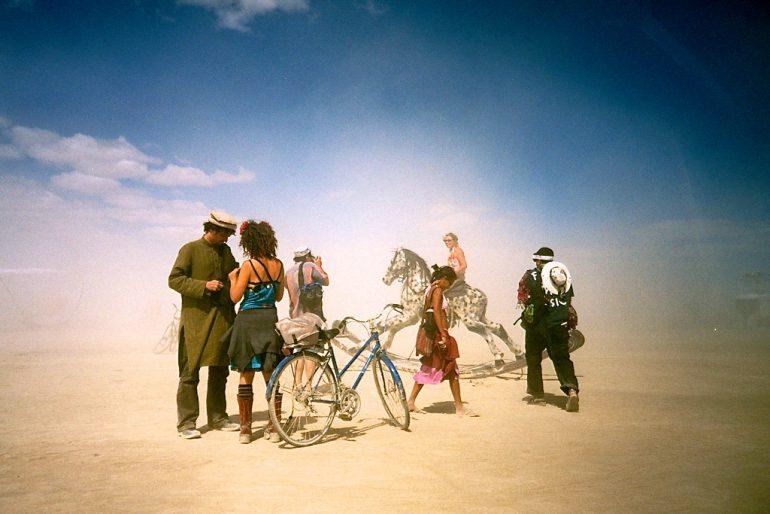 Menschen, ein Fahrrad und ein Schaukelpferd in der Wüste beim Burning Man