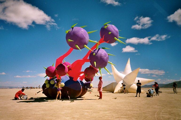 Menschen vor aufblasbaren Kunstwerken in der Wüste beim Burning Man 2004