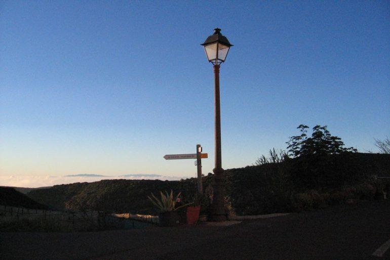 Lampe und Wegweiser vor Bergen und Sonnenuntergang