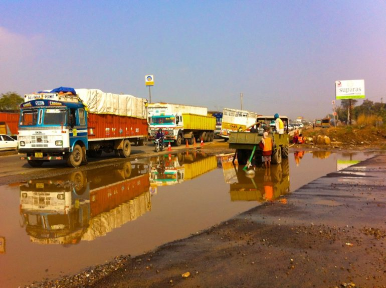 Renting an Enfield in India: Trucks on a wet road
