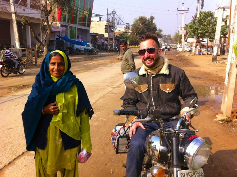 Renting an Enfield in India: Marco Buch on a Royal Enfield next to an Indian woman