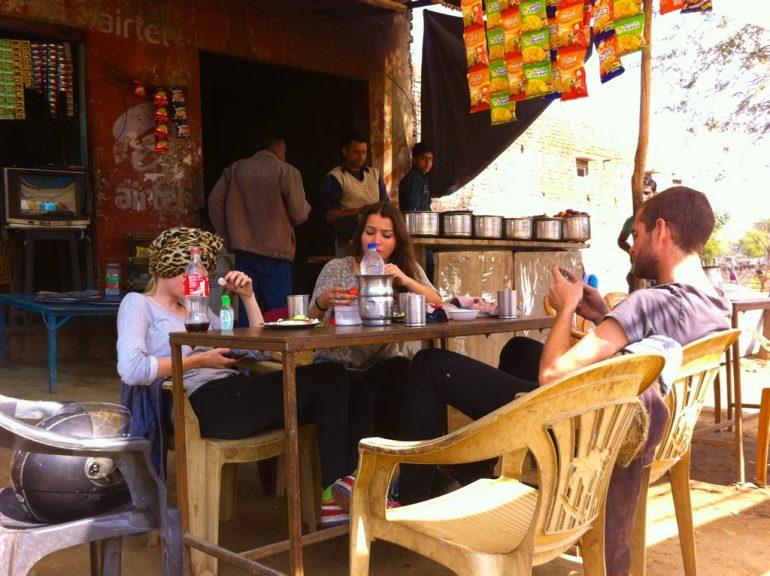 Enfield mieten in Indien: Westliche Touristen sitzen in einem Café am Strassnerand