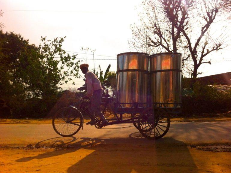 Mann auf einem Fahrrad mit Metallfässern
