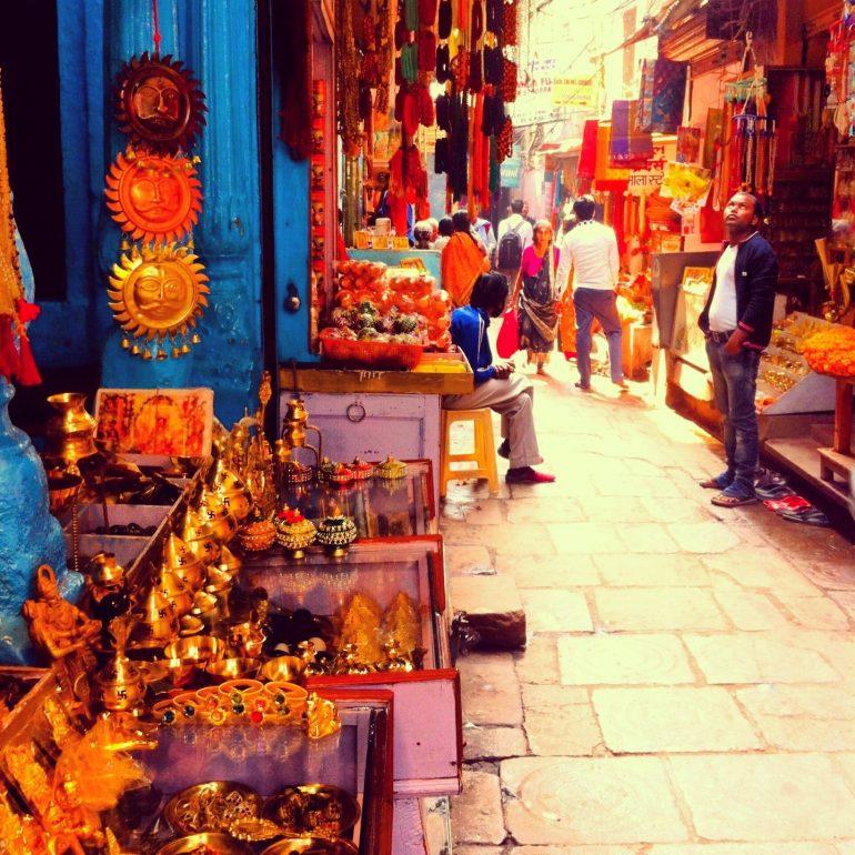 Menschen und kleine Statuen in einer Gasse von Varanasi