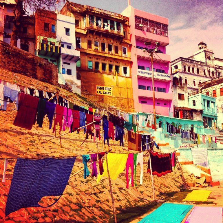 Wäsche trocknet vor bunten Häusern in Varanasi