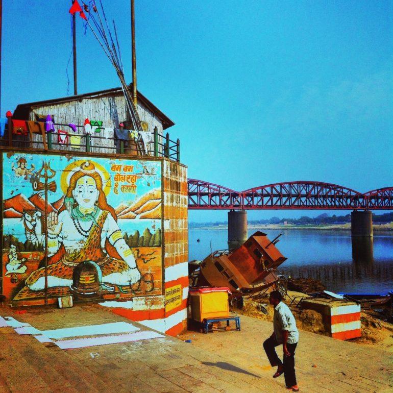 Mensch neben einem Shiva-Plakat am Ganges