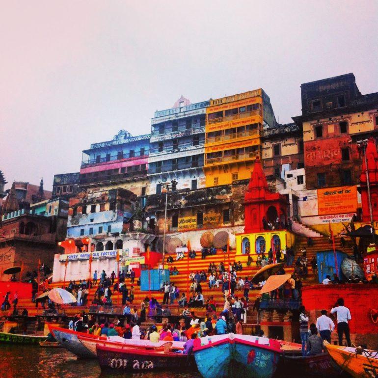 Menschen vor bunten Häusern am Ufer des Ganges