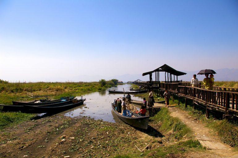 Boote  und Menschen neben einer Brücke in Myanmar