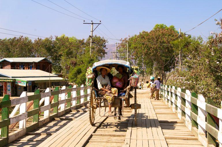 Kutsche mit Menschen auf einer Brücke in Myanmar