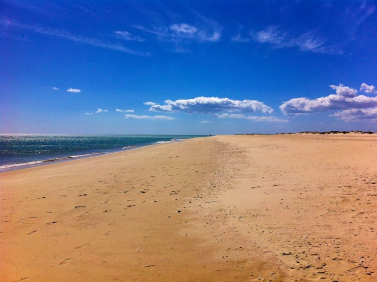 Agarve insider tips: Wide beach with clouds and ocean in Barril Beach