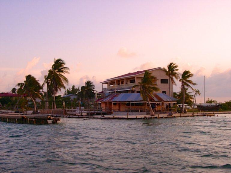 Haus, Meer und Palmen im Sonnenuntergang