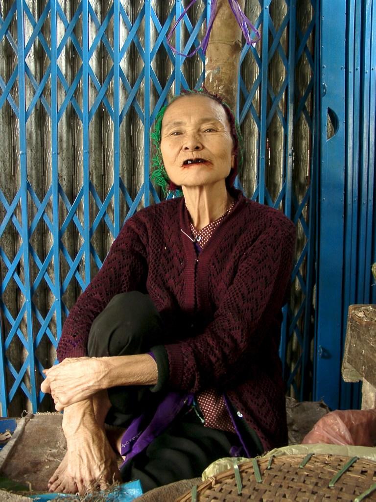 Lieblingsfotos: Frau vor blauem Zaun nahe Hoi An, Vietnam