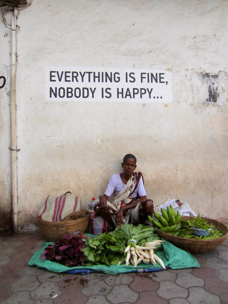 Verkäuferin mit Wandbeschriftung in Goa Indien