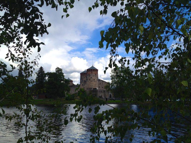 Blick durch Blätter auf die Burg von Olavinlinna