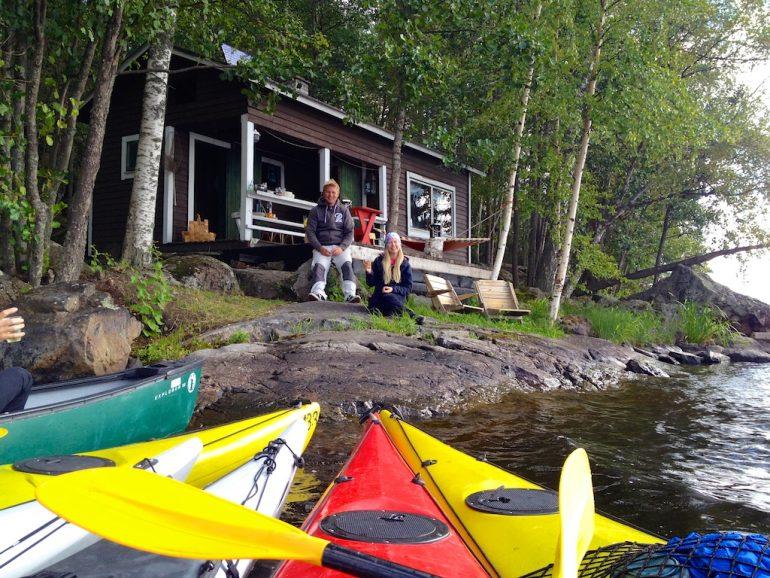 Zwei Menschen mit Kayaks vor ihrer Hütte in Finnland