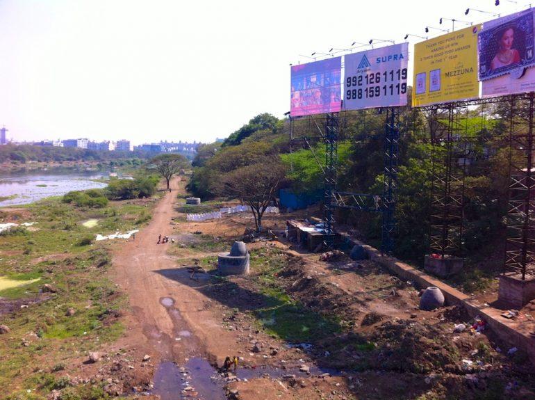 Werbeplakate und ein Feldweg am Flussufer in Pune