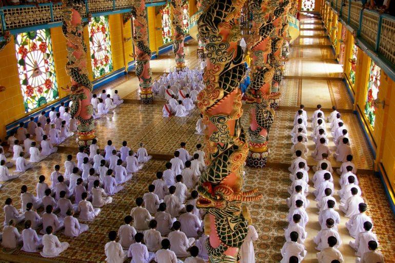 Betende in der Gebetshalle des Cao Dai Tempel