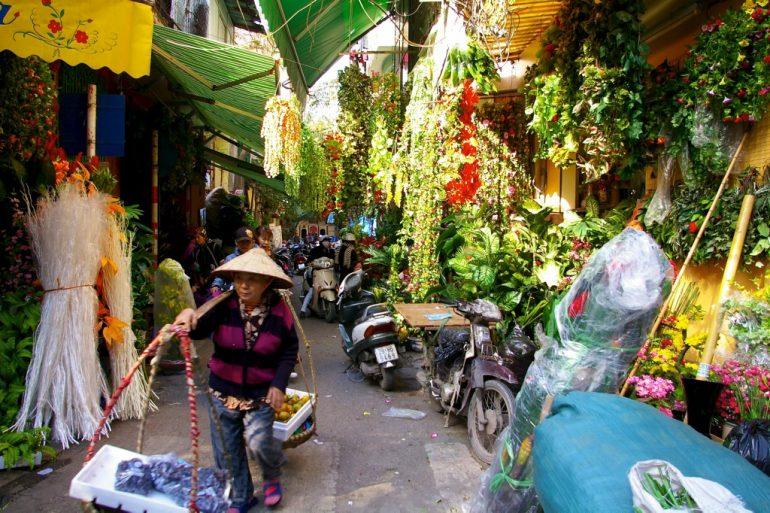 Frau mit Waren in einer Gasse in Hanoi