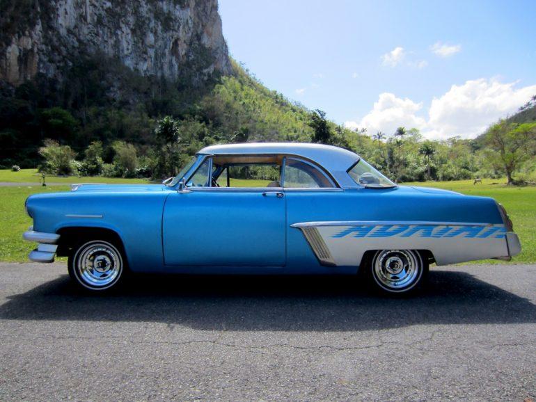 Kuba Autos: Blaues Auto vor Bergen