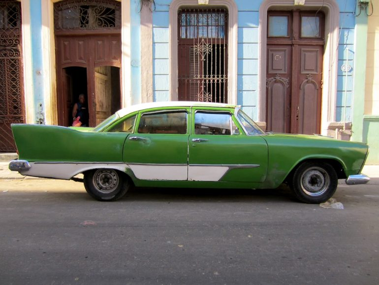 Cuba cars: Green US classic car in front of an old house