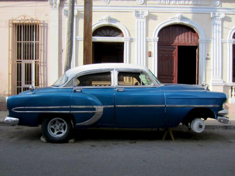 Blauer Oldtimer vor kubanischem Haus