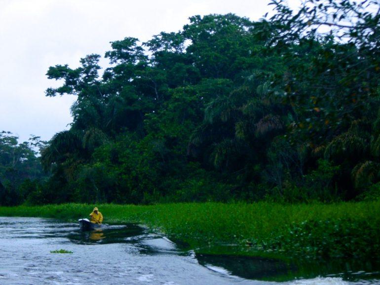Mann mit regenmantel in einem Boot auf einem Fluss