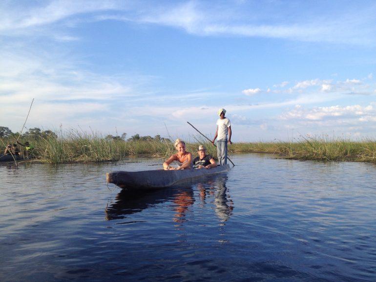 Teilneher eir Afrika Rundreise in einem Boot im Okavango-Delta