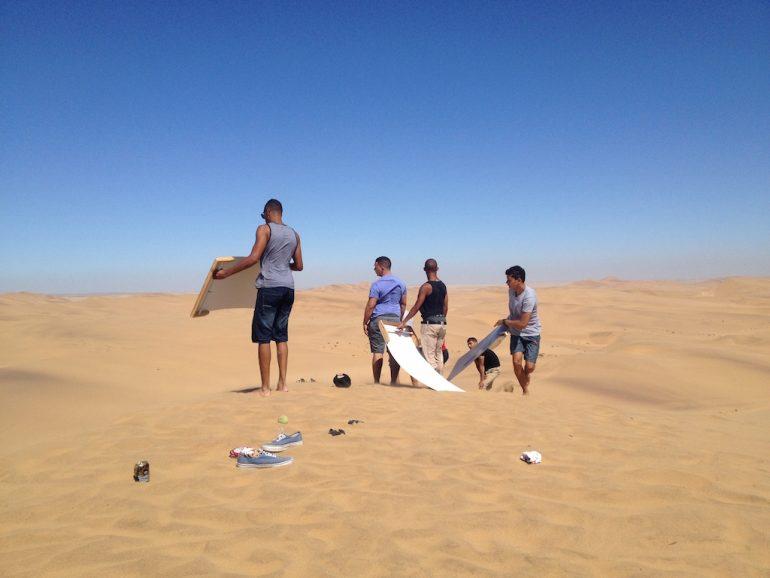 Menschen beim sandboarden in der Namib Wüste