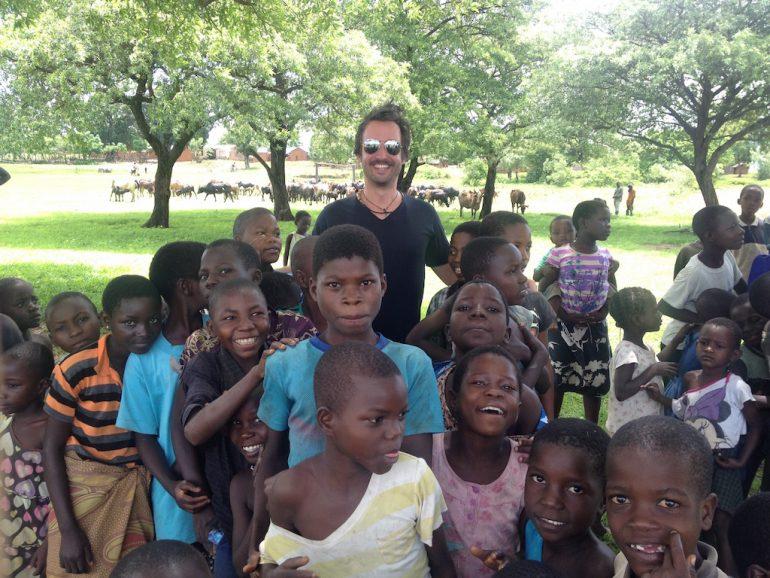 """""""Marco Buch"""" inmitten einer Gruppe Kinder in Malawi"""