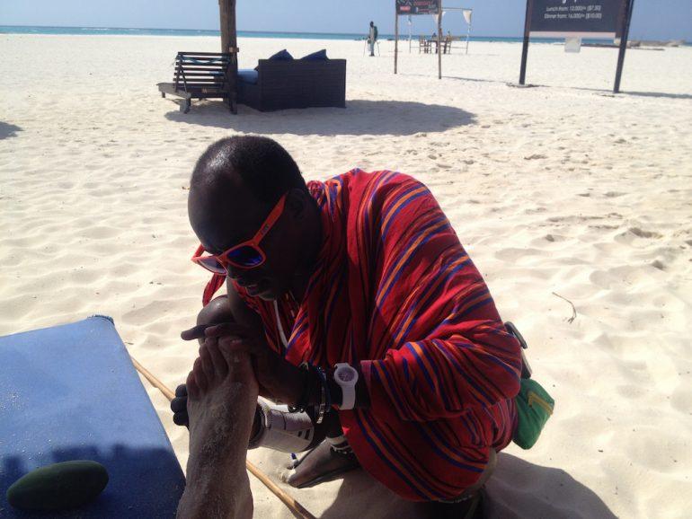 Ein Massai operiert Seeigelstacheln aus einem Fuss in Sansibar