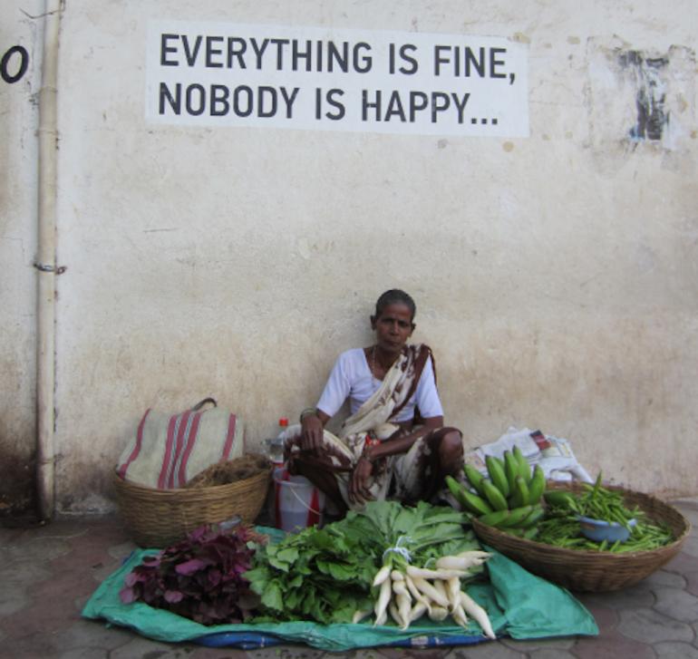 Verkäuferin vor Schild in Goa