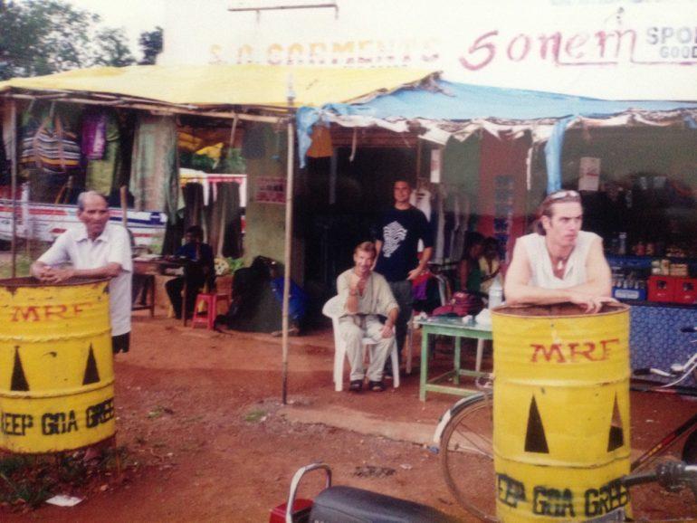 Menschen warten an Tonnen in Goa