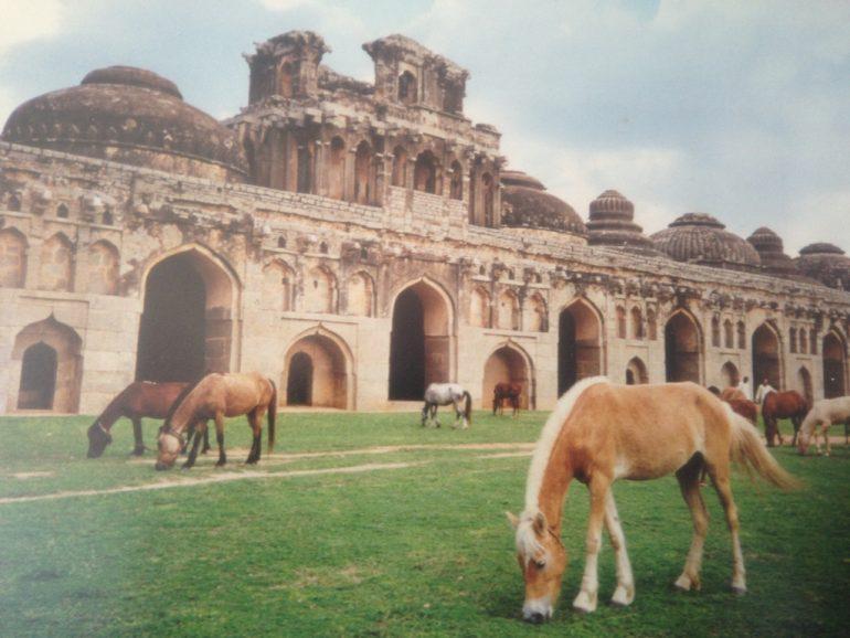 Pferde vor altem Gebäude in Hampi