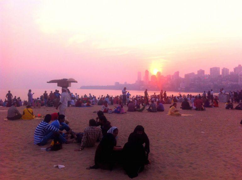 Schöne Fotos: Menschen im Sonnenuntergang am Strand in Chowpatty Beach, Mumbai