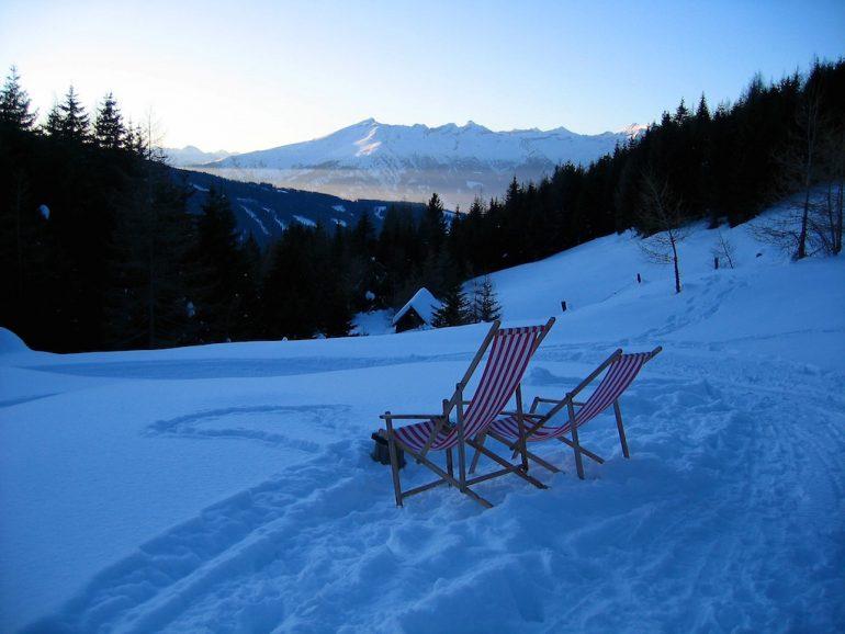 Schöne Fotos: Liegestühle im Schnee vor Bergkulsse in Tirol