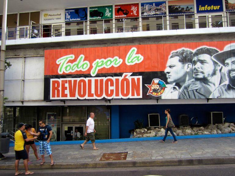 Menschen vor Revolutions-Schild in Havanna