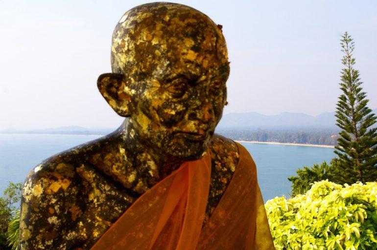 Thailand Highlights: Vergoldete Mönchsstatue vor einem Strand