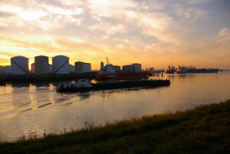 Schiffe und Silos im Sonnenuntergang über dem Rhein