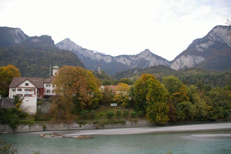 Häuser und Berge am Zusammenfluss Vorderrhein und Hinterrhein