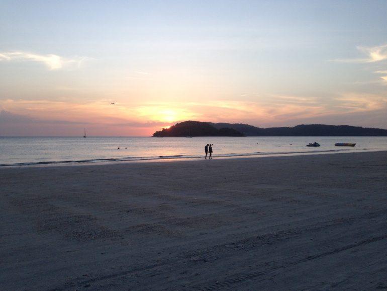 Menschen im Sonnenuntergang am Strand