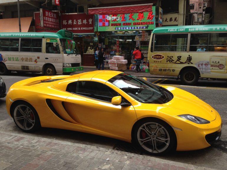 Hong Kong Sehenswürdigkeiten: Gelber Mc Laren vor bunten Geschäften