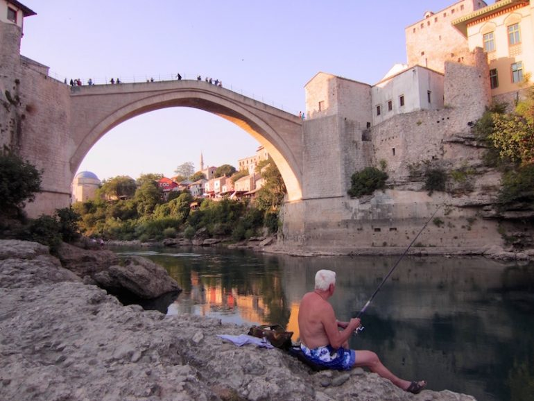 Best road trips: Man in front of the Stari Most bridge in Mostar