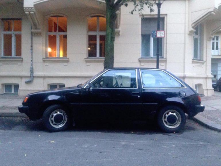 Oldtimer Berlin: Schwarzer Mitsubishi Colt vor Hauswand.