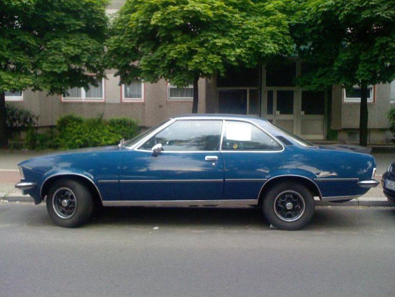 Oldtimer Berlin: Blaues Opel Commodore B Coupé vor grünen Bäumen