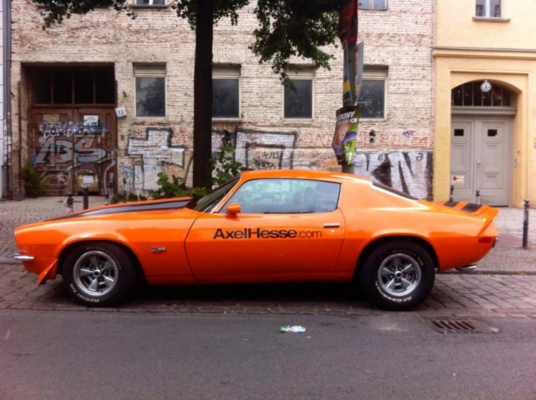Oldtimer Berlin: Pontiac Firebird in orange vor Hauswand