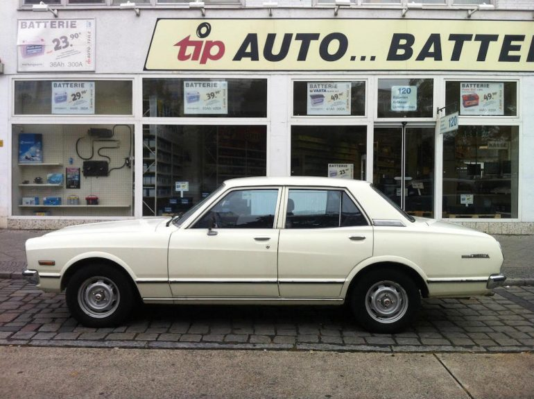 Oldtimer Berlin: Weißer Toyota Carina vor Auto-Geschäft